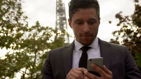 Young attractive businessman in a black suit sends a message on a cell phone on the background of the Eiffel Tower
