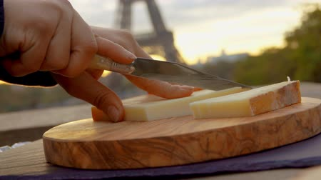 eiffel : Hand is slicing hard goat cheese on a wooden board against the backdrop of the Eiffel Tower, Paris, France Stock Footage