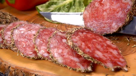 fumado : Sharp knife cut a slice of dried sausage in herbs on a wooden board on the background of greenery Vídeos