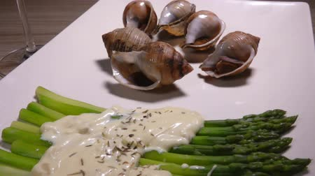caracol : Cooked sea escargo snails with a side dish of green asparagus with cheese sauce