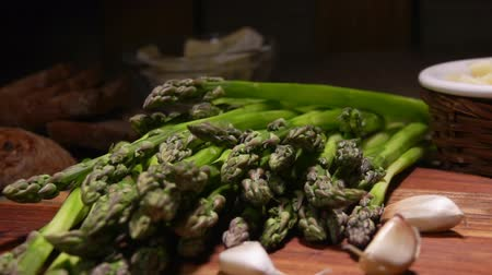 kuşkonmaz : Peeled stems of green asparagus fall on the table on a background of cheese and garlic. Cheese Sauce Ingredients Stok Video