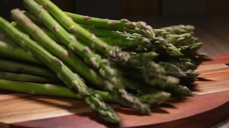 espargos : Rope is untied on a bunch of fresh green asparagus and the stems are scattered on the table Stock Footage