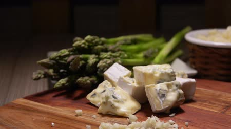 espargos : Ingredients for cheese sauce on a board on background of green asparagus - finely chopped garlic and blue cheese cubes