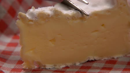 laktóz : Piece of soft appetizing camambert cheese is cut with a fork on the background of a red and white vichy napkin vichy