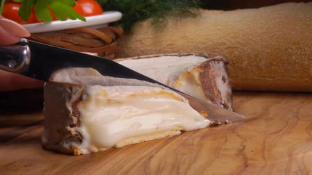 пармезан : Soft creamy French Epoisses cheese in brown mold cut with a knife on a wooden board on the background of baguette