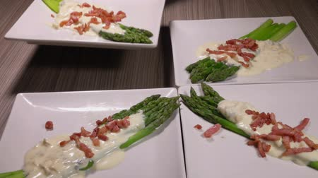 espargos : Square plate with asparagus in a cheese sauce with ham is put on the table with other plates. Beautiful serving of traditional French cuisine Stock Footage
