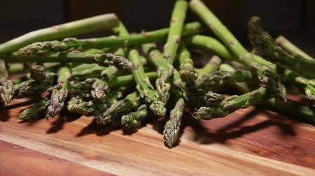espargos : Bunch of fresh green asparagus falls and bounces on a wooden board