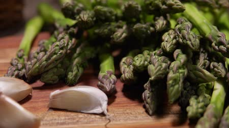 пармезан : Close up of garlic cloves and spears of green peeled asparagus on a wooden board. Cheese Sauce Ingredients