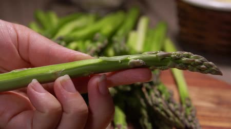 asperges : Peeled stems of green asparagus fall on the table on a background of cheese and garlic. Cheese Sauce Ingredients Stockvideo