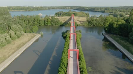 Modern architectural complex in the city of Cergy on the Oise River, France. Aerial shot of a conceptual bridge with red arches. Beautiful play of light and shadow Стоковые видеозаписи