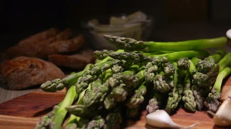 espargos : Peeled stems of green asparagus fall on the table on a background of cheese,bread and garlic. Cheese Sauce Ingredients