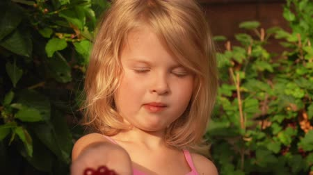 красная смородина : Blond girl showing a bunch of red currants in her hand. Girl eating currant and smiling at camera