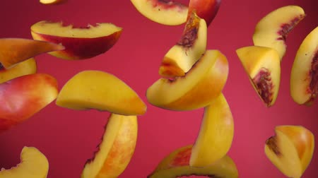 ressalto : Delicious juicy slices of peaches bounce on a red background close up in slow motion Vídeos