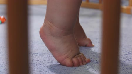 Close-up of baby feet standing on toes on a Blue Blanket in Playpen