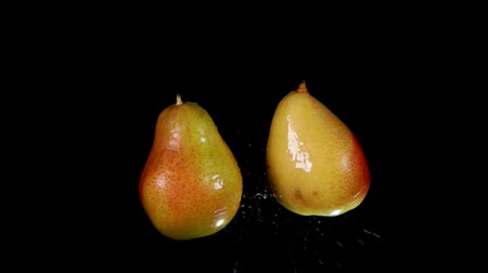 Two juicy tasty pears collide with each other on a black background Стоковые видеозаписи