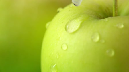 Drop of water flows down a large ripe Juicy green apple. Slow motion super close-up