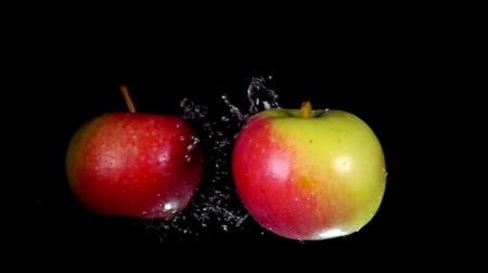 bounce : Two wet red-green apples collide with each other and scatter in different directions. Extreme close-up slow motion Stock Footage