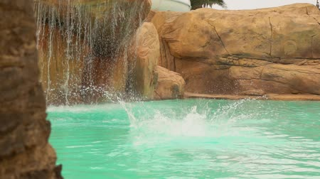 Young attractive man dives into the turquoise water of a swimming pool in a water park on the background of a waterfall