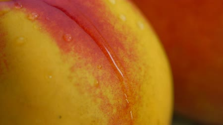 brzoskwinie : Close-up of a drop of water flowing over the surface of a ripe juicy peach