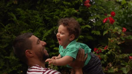 Handsome dad in a striped T-shirt throws up a happy baby boy outdoors in the garden