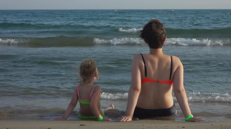 Mom and daughter in swimsuits are sitting on the seashore with their backs to the camera and watching the waves