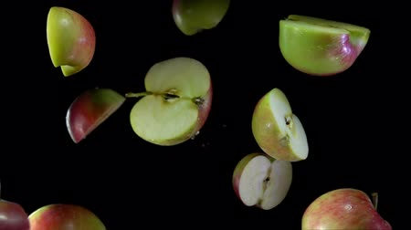 bounce : Halves of delicious apples fly up and rotate on a black background Stock Footage