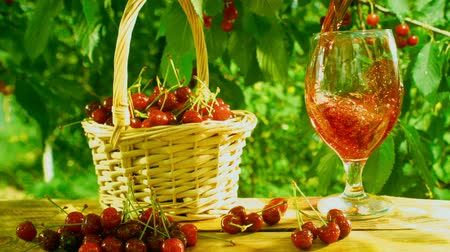 Delicious cherry juice is poured into a glass on a table with basket full of ripe berries outdoors on a bright sunny day Wideo