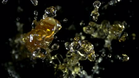 bounce : Wave of splashes and drops of apple juice fly on a black background Stock Footage