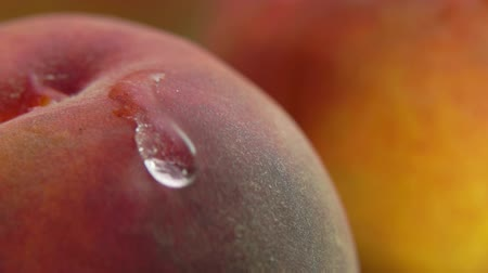 Shining drop of water flows down the surface of a ripe juicy peach