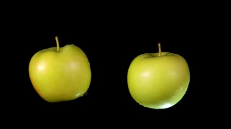 bounce : Two wet green apples collide with each other and scatter in different directions on the black background. Close-up slow motion