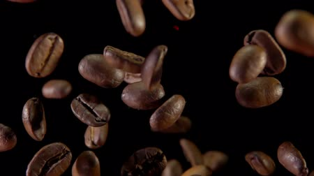 Roasted coffee beans fly and spin on a black background