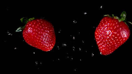 Two delicious red strawberries collide each other with a water splash and rotate on a black background