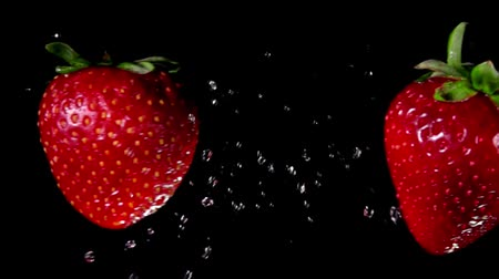 bűbájos : Two juicy tasty large red strawberries collide with splashes of water and rotate on a black background Stock mozgókép