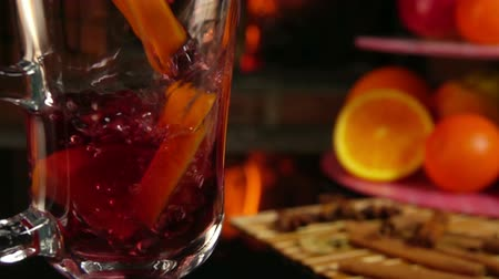 vin brulè : Mulled wine with oranges is poured into a glass cup against the background of the fireplace
