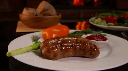 baharatlı alman sosisi : White plate with grilled sausages and vegetables on the background of a burning fireplace Stok Video