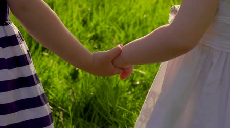 Super close up of two little girls holding their hands outdoors in sunny day in park