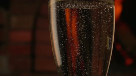 homely : Champagne is poured into a tall glass on a background of fire in fireplace Stock Footage