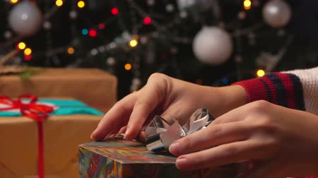 Close-up of the hands of packing gifts on the background of the Christmas tree 影像素材