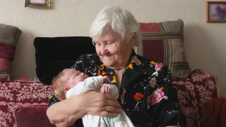 Young woman passes her little baby into the arms of happy grandmother