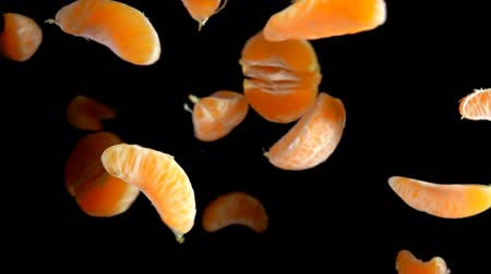 Peelled pieces of tangerine are flying and spinning on a black background in slow motion Stock mozgókép
