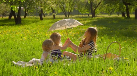 Three girls in beautiful striped dresses are sitting on the lawn in the garden and reading a book under vintage sun umbrella Стоковые видеозаписи