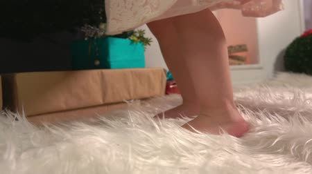 Adorable baby girls feet on the toes near Christmas tree on the background of a decorative fireplace
