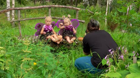 Photographer takes pictures of girls playing violet butterflies. Girls wear butterfly wings Стоковые видеозаписи