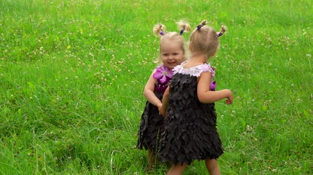 Two blond little girls in a purple fantasy dresses made of leaves and flowers are holding their hand and dancing on the meadow