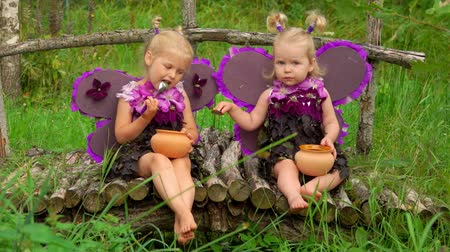 Beautiful girls with butterfly wings eat honey from pots. Children pretend to be purple butterflies Стоковые видеозаписи