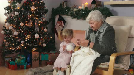 Elderly woman knits a white blanket sitting in a chair with a little cute girl in pink dress next to the Christmas tree. Grandmother shows to her little granddaughter how to knit