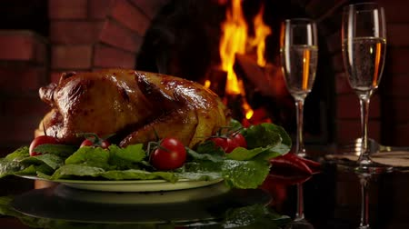 kabarcıklı : Plate with delicious baked chicken is placed on the table on the background of fireplace and glass of champagne. Festive christmas table setting