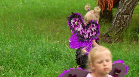 Two girls in a violet butterfly costumes walking on the green lawn. Children pretend to be purple butterflies