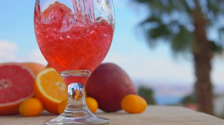 Multifruit juice is poured into a wine-glass against the background of the sea landscape, close-up camera motion Stock mozgókép