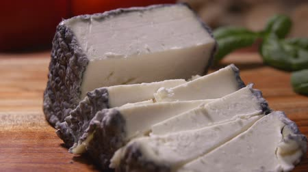 laktóz : Double tooth fork takes a piece of soft goat delicious cheese with grey mold from a wooden cutting board